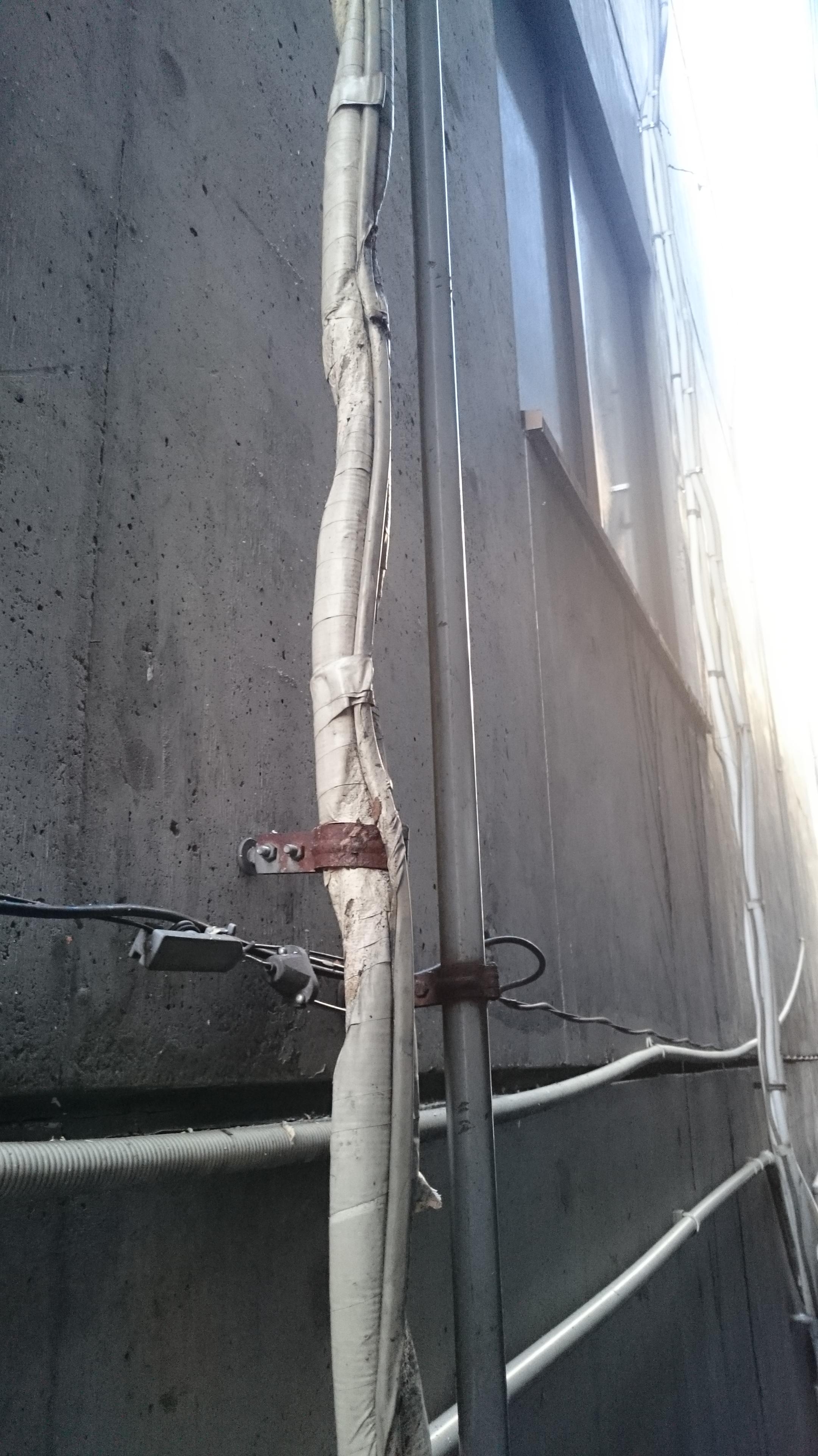 建造物の隙間にひっそりと佇む8メートルのエアコンホース